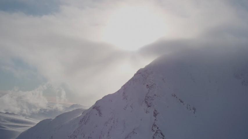 4K stock footage aerial video flying by a snowy mountain capped by sunlit clouds, Chugach Mountains, Alaska Aerial Stock Footage | AK0001_1916