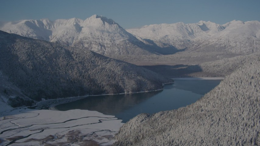 4K stock footage aerial video descending toward Carmen Lake surrounded by snow covered mountains, Alaska Aerial Stock Footage | AK0001_1921