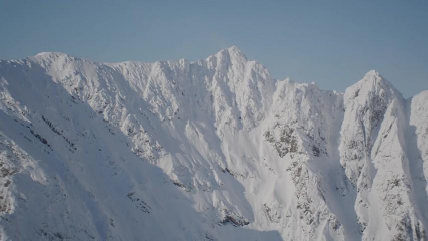 4K stock footage aerial video pan across jagged, snowy mountain range in Chugach Mountains, Alaska Aerial Stock Footage   AK0001_1973