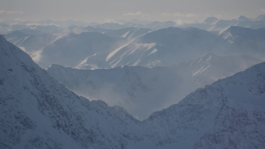 4K stock footage aerial video snow covered windblown mountains and low clouds in Kenai Mountains, Alaska Aerial Stock Footage | AK0001_1976