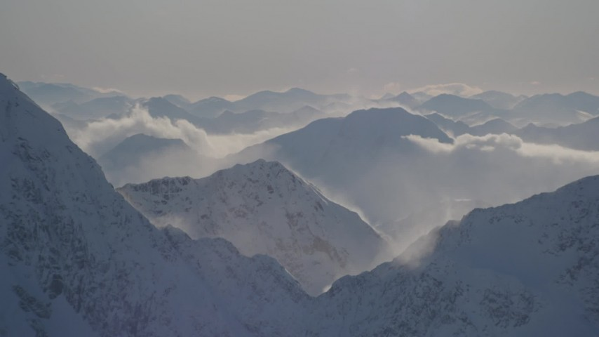 4K stock footage aerial video snowy, windblown mountain ranges and low clouds in Kenai Mountains, Alaska Aerial Stock Footage | AK0001_1978