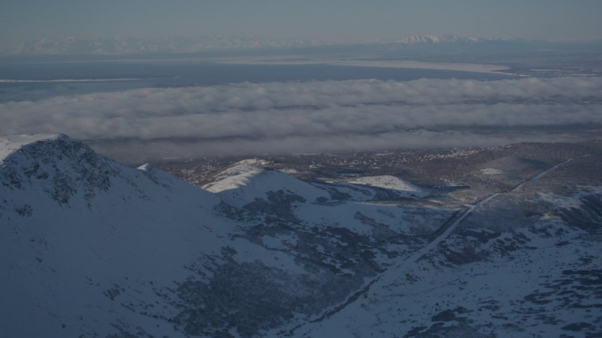 4K stock footage aerial video cloud covered Anchorage, seen from snowy Chugach Mountains, Alaska Aerial Stock Footage | AK0001_1996
