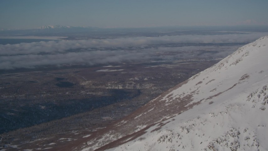 4K aerial stock footage video flying by snowy mountain peak toward wooded foothills near Anchorage, Alaska Aerial Stock Footage | AK0001_2002