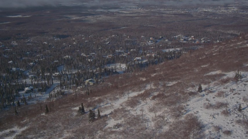 4K stock footage aerial video flying over a snowy hill toward a residential neighborhood in Anchorage, Alaska Aerial Stock Footage   AK0001_2005