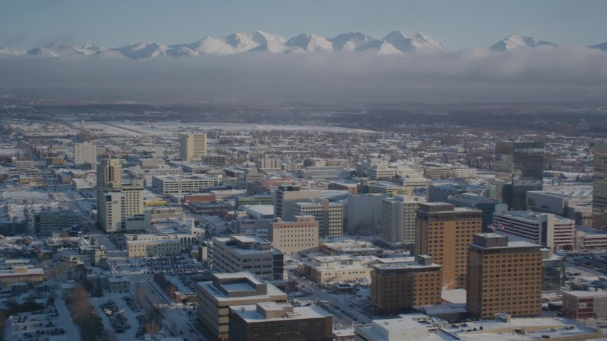 4K stock footage aerial video snowy downtown Anchorage with cloud covered Chugach Mountains, Alaska Aerial Stock Footage | AK0001_2017