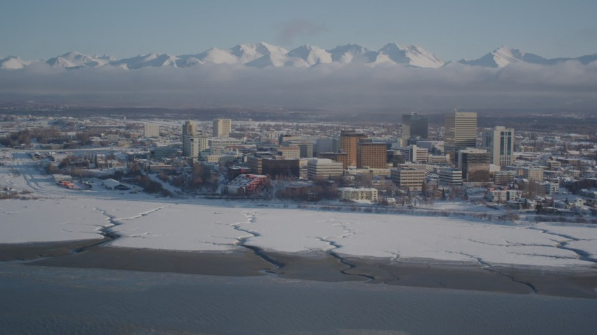 4K stock footage aerial video snowy Downtown Anchorage, descend toward frozen shore of Cook Inlet, Alaska Aerial Stock Footage | AK0001_2020