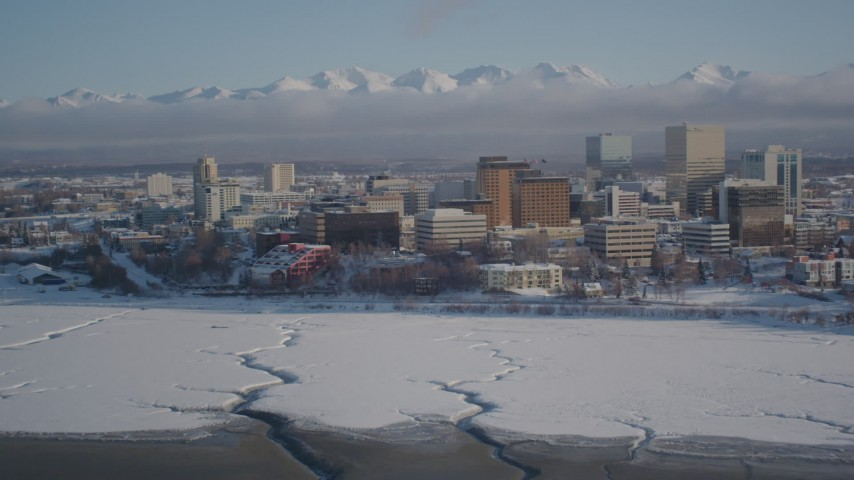4K stock footage aerial video fly over frozen shore of Cook Inlet toward snowy Downtown Anchorage, Alaska Aerial Stock Footage | AK0001_2021