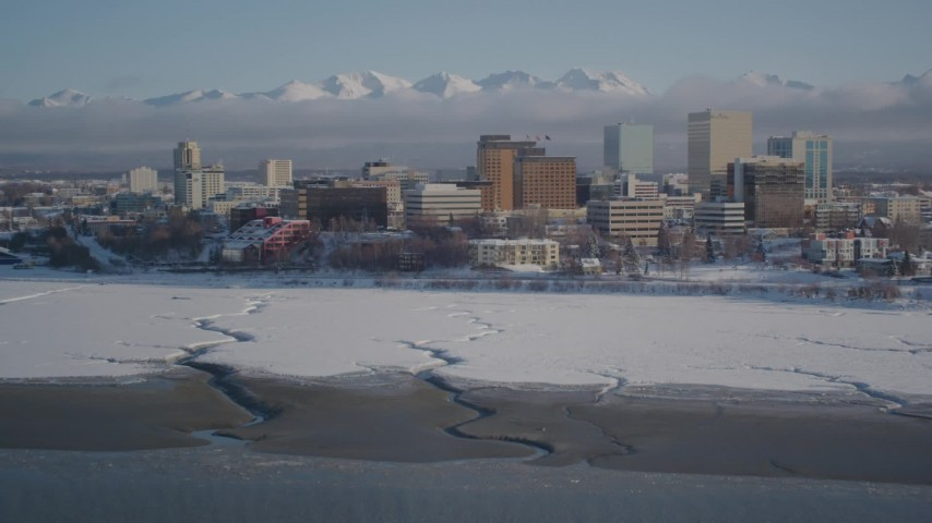 4K stock footage aerial video tilt up from surface of Cook Inlet revealing snowy Downtown Anchorage, Alaska Aerial Stock Footage | AK0001_2023