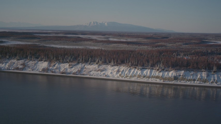 4K stock footage aerial video flying over snowy, wooded shore of Point MacKenzie, Alaska Aerial Stock Footage | AK0001_2033