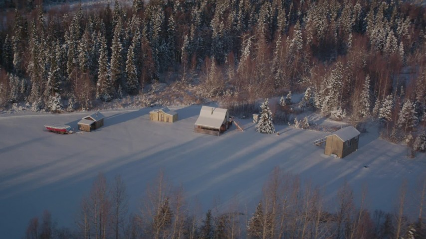 4K stock footage aerial video fly by small cabins near snowy forest in Point MacKenzie, Alaska Aerial Stock Footage | AK0001_2036