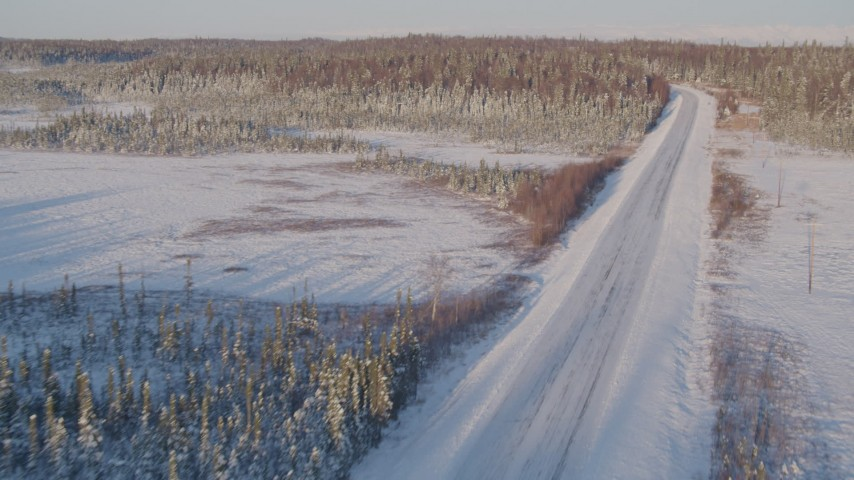 4K stock footage aerial video following a deserted snowy rural highway in Point MacKenzie, Alaska Aerial Stock Footage | AK0001_2046