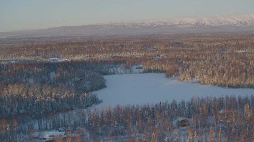 4K stock footage aerial video houses near frozen lake, snowy forest in Knik-Fairview, Alaska, sunset Aerial Stock Footage | AK0001_2068