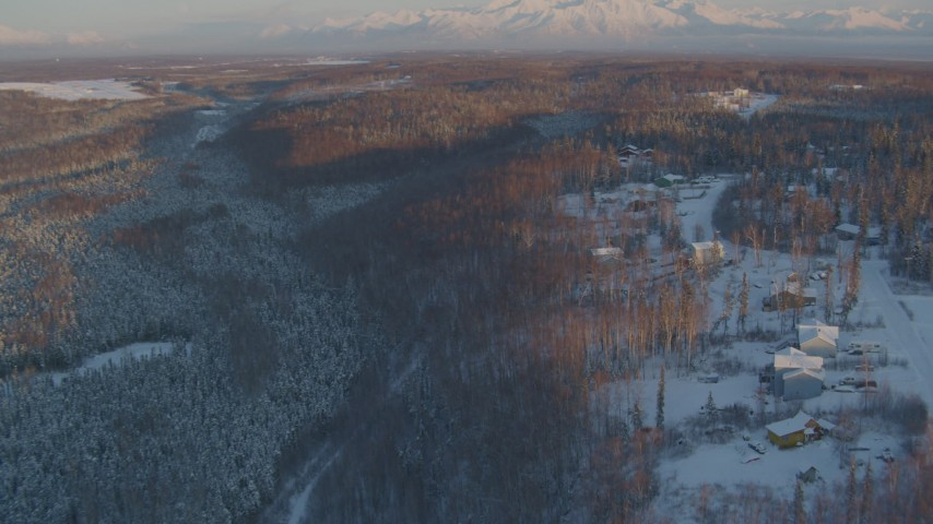 4K stock footage aerial video approach Shawn Field, reveal snowy neighborhood in Wasilla, Alaska, sunset Aerial Stock Footage | AK0001_2071