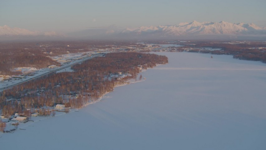 4K stock footage aerial video Lucile Lake, moon over snowy Chugach Mountains at sunset, Wasilla, Alaska Aerial Stock Footage | AK0001_2076