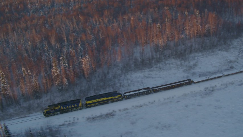4K stock footage aerial video tracking a train running by snowy trees at sunset, Wasilla, Alaska Aerial Stock Footage | AK0001_2079
