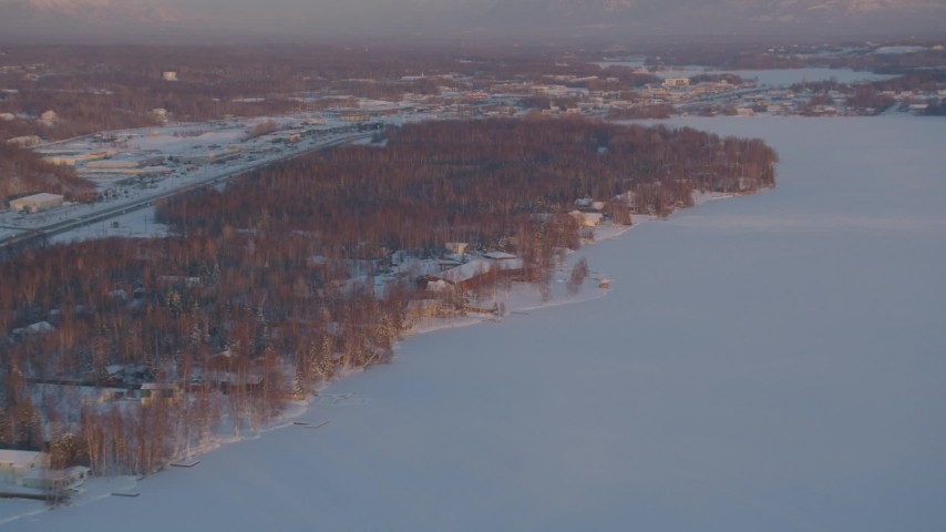4K stock footage aerial video fly over Lucile Lake, homes on the snowy shore, Wasilla, Alaska, sunset Aerial Stock Footage | AK0001_2083