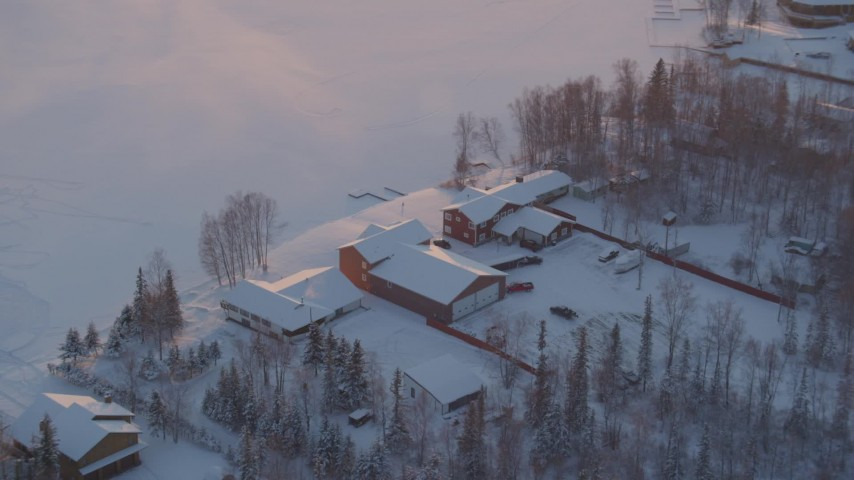 4K stock footage aerial video orbiting a snow covered house on Lucile Lake at sunset, Wasilla, Alaska Aerial Stock Footage | AK0001_2084