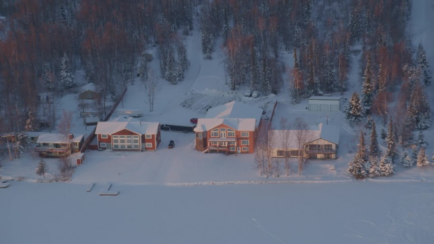 4K stock footage aerial video flying away from snow covered houses on Lucile Lake at sunset, Wasilla, Alaska Aerial Stock Footage | AK0001_2086