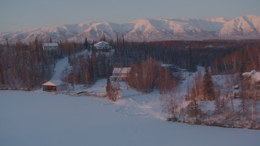 4K stock footage aerial video fly by snow covered homes on frozen Cottonwood Lake, Wasilla, Alaska, twilight Aerial Stock Footage | AK0001_2090