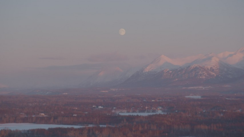 4K stock footage aerial video the moon over the snow covered Chugach Mountains at twilight, Wasilla, Alaska Aerial Stock Footage | AK0001_2092