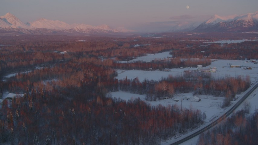 4K stock footage aerial video fly over snow covered neighborhoods, reveal mountains, Palmer, Alaska, twilight Aerial Stock Footage | AK0001_2094