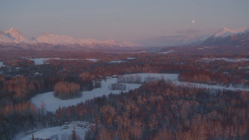 4K stock footage aerial video fly over snowy rural homes, reveal moon over mountains, Palmer, Alaska, twilight Aerial Stock Footage | AK0001_2095