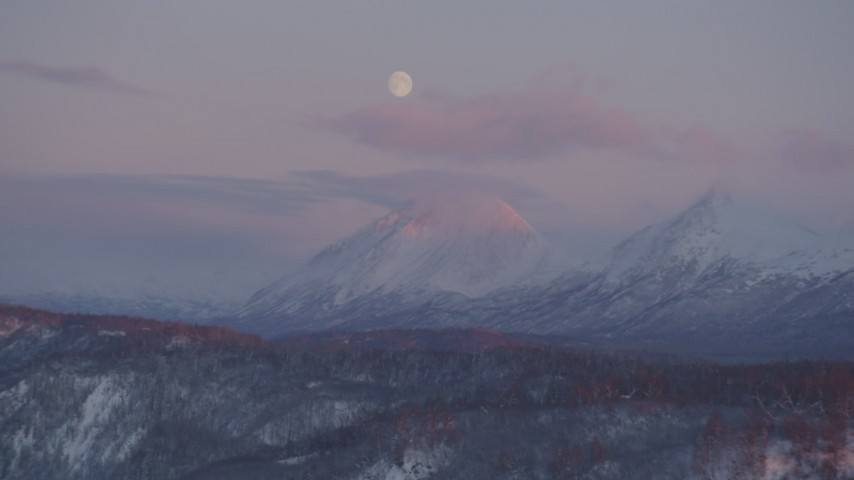 4K stock footage aerial video the moon over the snow covered Chugach Mountains at sunset, Alaska Aerial Stock Footage | AK0001_2101