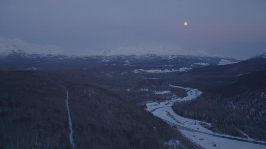 4K stock footage aerial video moon over snowy Talkeetna Mountains, Matanuska River Valley, Alaska, twilight Aerial Stock Footage | AK0001_2116