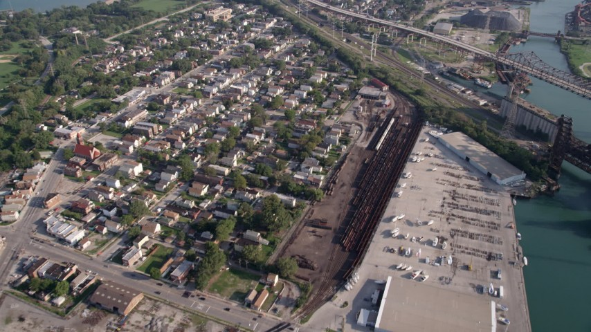 5K aerial video flying away from Chicago Skyway, neighborhood, and  warehouses by the river, East Side Chicago, Illinois