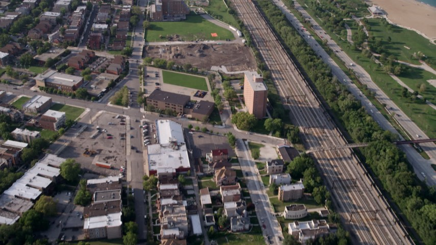 5K stock footage aerial video tilt from homes by the train tracks to reveal the Downtown Chicago skyline, Illinois Aerial Stock Footage | AX0001_013