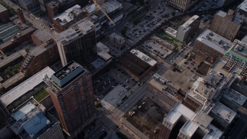 5K aerial video tilt up from downtown parking lots and buildings to reveal Willis Tower, Downtown Chicago, Illinois Aerial Stock Footage | AX0001_024