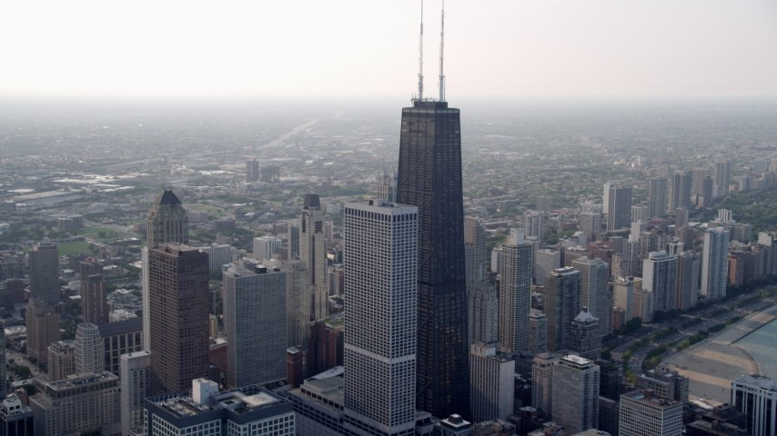 5K video of the top of John Hancock Center, hazy, Downtown Chicago, Illinois Aerial Stock Footage | AX0001_039