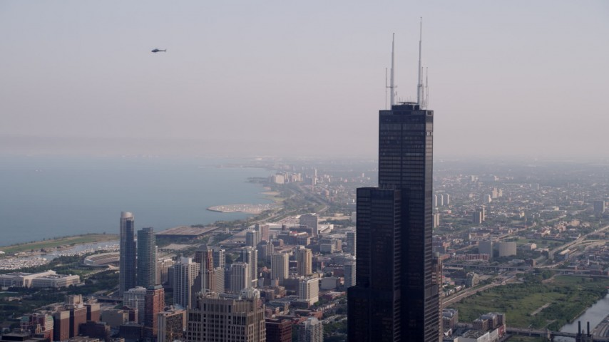 5K stock footage aerial video of an orbit of the top of the Willis Tower in Downtown Chicago, on a hazy day, Illinois Aerial Stock Footage | AX0001_044