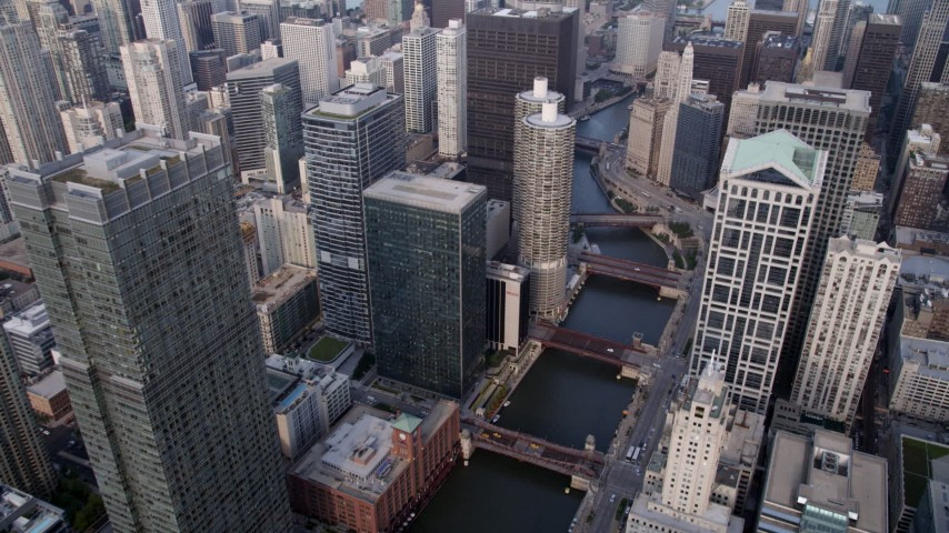 5K stock footage aerial video following the Chicago River through downtown skyscrapers toward Marina City, Downtown Chicago, Illinois Aerial Stock Footage | AX0001_047