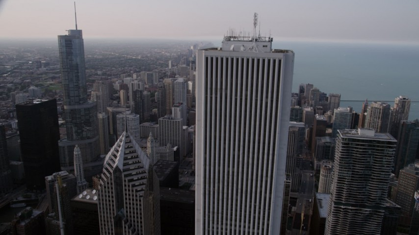 5K aerial video flying by Aon Center, revealing Trump International and John Hancock Center in Downtown Chicago, Illinois Aerial Stock Footage | AX0001_052