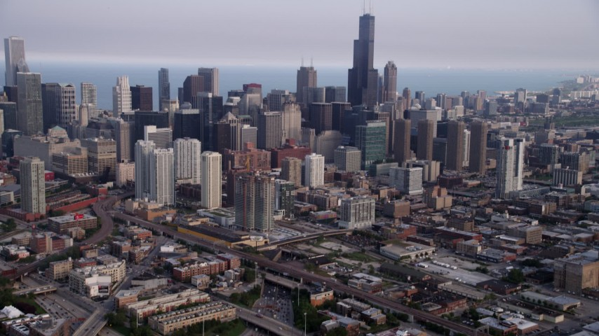 5K stock footage aerial video tilting up from heavy traffic on Interstate 90 and 94, revealing Downtown Chicago skyscrapers, Illinois Aerial Stock Footage AX0001_065