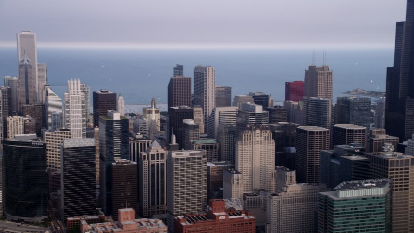 5K stock footage aerial video panning across Downtown Chicago on a hazy day to reveal Willis Tower, Illinois Aerial Stock Footage | AX0001_068