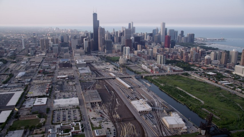 5K stock footage aerial video tiliting from train yards by the Chicago River, revealing downtown skyline on a hazy day, Downtown Chicago, Illinois Aerial Stock Footage | AX0001_076