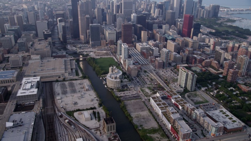5K stock footage aerial video tilting from Metra Railroad Yard and Chicago River, reveal hazy Downtown Chicago, Illinois Aerial Stock Footage | AX0001_078