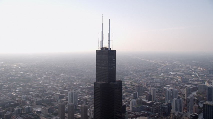5K stock footage aerial video orbiting the top of Willis Tower in Downtown Chicago, on a hazy day, Illinois Aerial Stock Footage | AX0001_082