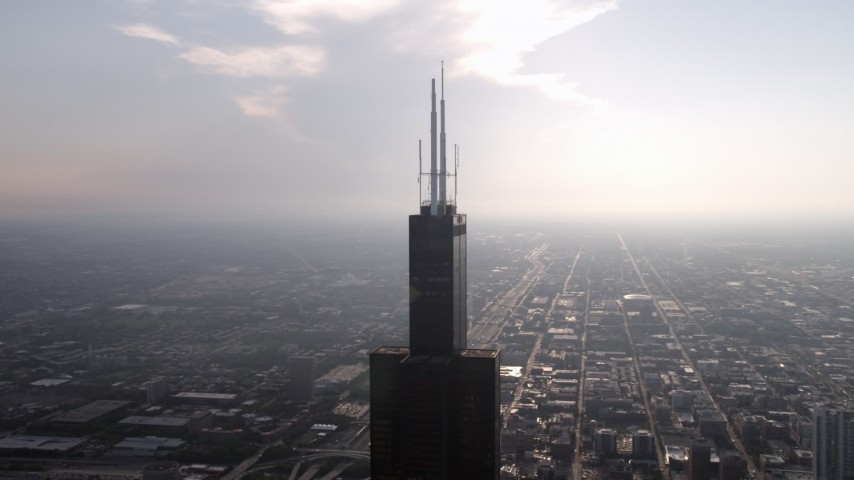 5K aerial video of the top of the Willis Tower on a hazy day, Downtown Chicago, Illinois Aerial Stock Footage | AX0001_083