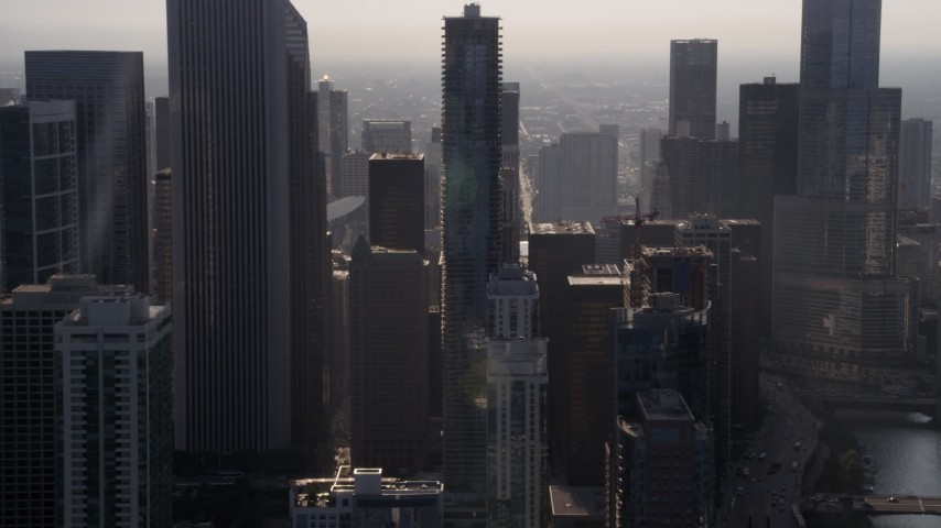 5K stock footage aerial video flying by downtown Chicago skyscrapers, revealing Jay Pritzker Pavilion, on a hazy day, Illinois Aerial Stock Footage | AX0001_094
