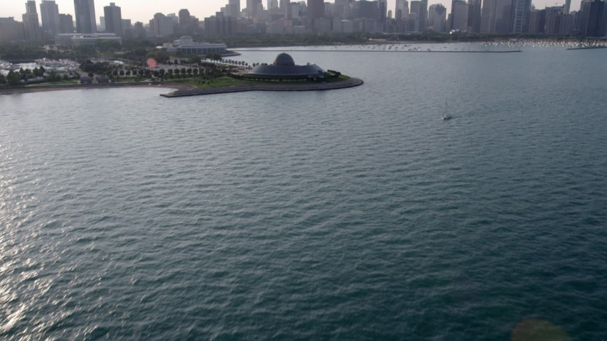5K stock footage aerial video tilt from the lake to reveal Adler Planetarium and Downtown Chicago skyline, Illinois Aerial Stock Footage | AX0001_099