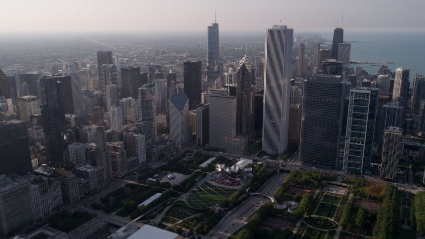 5K stock footage aerial video fly over Grant Park, and tilt to Cloud Gate sculpture and Jay Pritzker Pavilion, Downtown Chicago, Illinois Aerial Stock Footage | AX0001_103