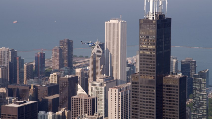 5K aerial video of a helicopter hovering near Willis Tower Skydeck in Downtown Chicago, on a hazy day, Illinois Aerial Stock Footage | AX0001_112