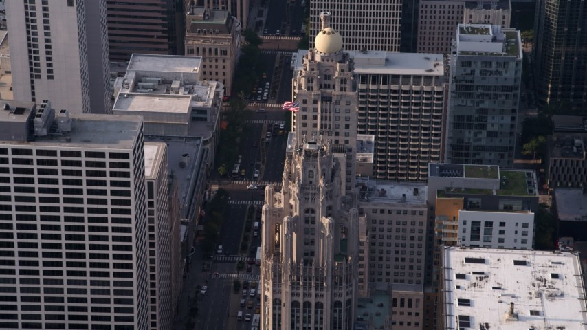 5K aerial  video approach flag flying at top of Tribune Tower in Downtown Chicago, Illinois Aerial Stock Footage | AX0001_118