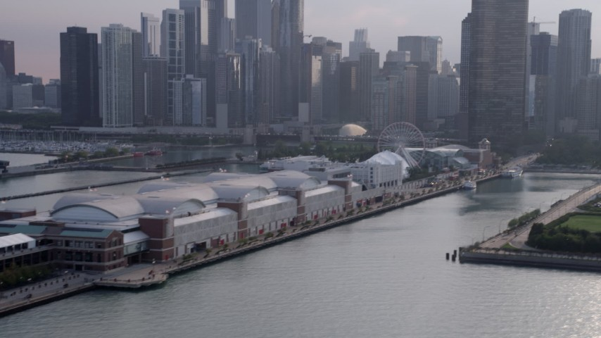 5K stock footage aerial video tilting up from Navy Pier to downtown Chicago skyscrapers, Illinois Aerial Stock Footage | AX0001_126