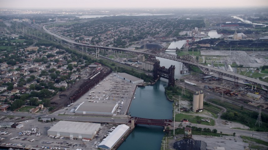 5K aerial video following Calumet River toward the High Bridge and Chicago Skyway, on a hazy day, Illinois Aerial Stock Footage AX0001_164
