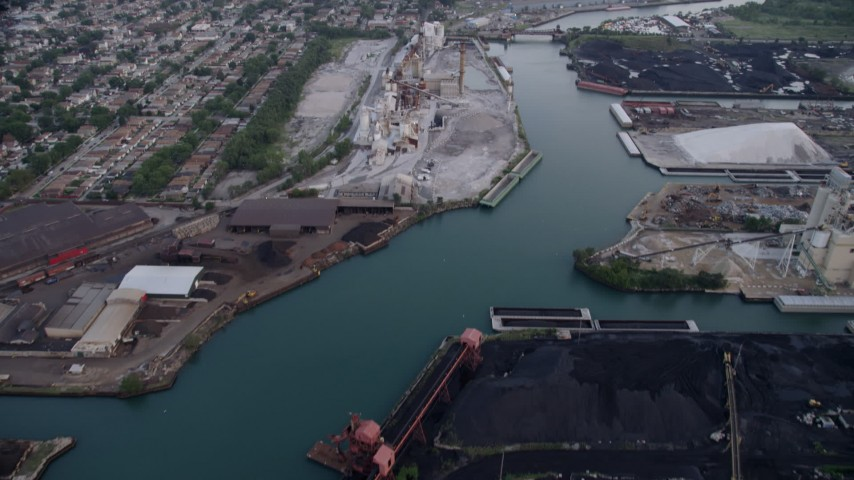 5K aerial video tilt from piles of petroleum coke by the Calumet River to reveal more industrial buildings, East Side Chicago, Illinois Aerial Stock Footage | AX0001_167