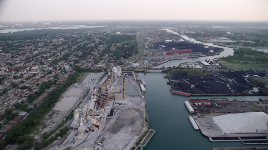 5K aerial video following Calumet River toward bridge between lime plant and petroleum coke, East Side Chicago, Illinois Aerial Stock Footage | AX0001_168